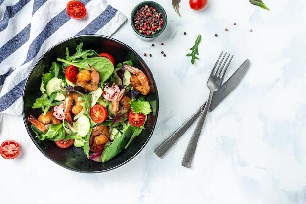 Салат из морепродуктов с копчеными креветками, помидорами черри, огурцом и смешанными листьями. баннер, место рецепта меню для текста, вид сверху.