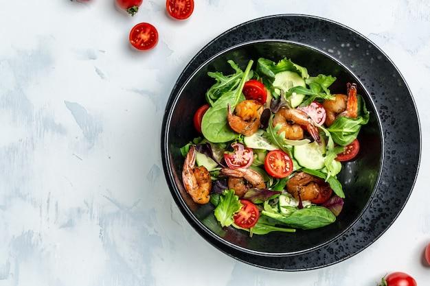 Салат из морепродуктов с копчеными креветками, помидорами черри, огурцом и смешанными листьями. концепция здорового питания. детокс-диета. вегетарианский обед. похудание, вид сверху.