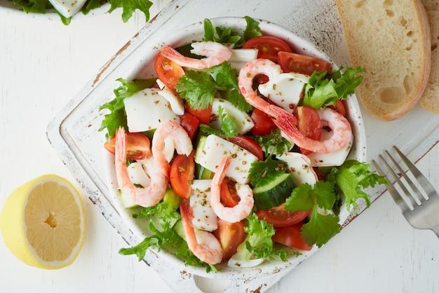 Салат из морепродуктов с кальмарами, креветками, огурцами, помидорами и листьями салата. lchf, fodmap, палео диета.