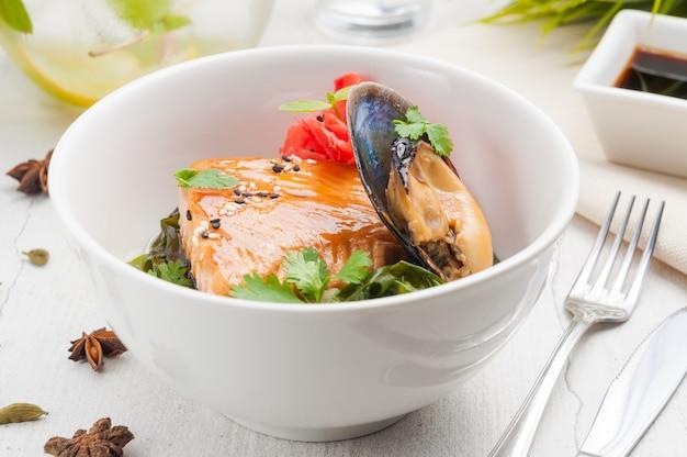 Стейк из лосося с морепродуктами с мидиями в белой миске