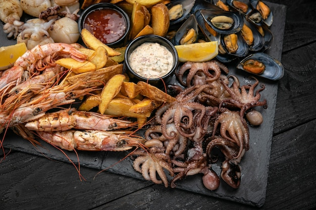 Морепродукты набор морепродуктов и соусов на грифельной доске на темном деревянном столе