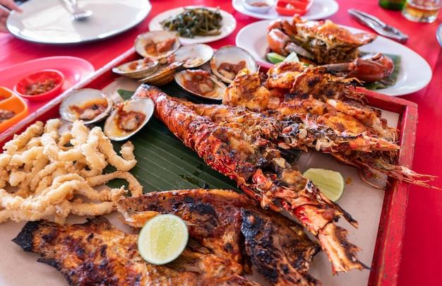 Набор морепродуктов с омарами, крабами, рыбой, креветками, моллюсками на деревянном подносе в ресторане бали