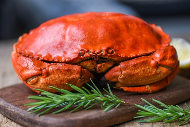 Seafood shellfish steamed red crab or boiled stone crab - fresh crab with ingredients lemon rosemary on wooden board