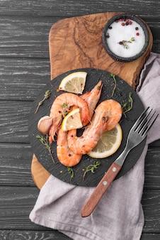 Креветки из морепродуктов на деревянной доске и столовые приборы