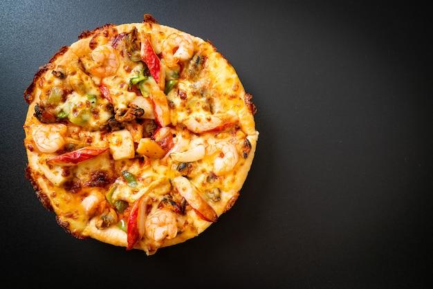 シーフード(エビ、タコ、ムール貝、カニ)のピザを木製トレイに載せる