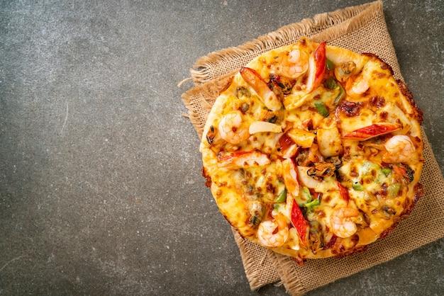 Пицца из морепродуктов (креветки, осьминоги, мидии и крабы) на деревянном подносе