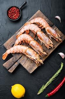 검은 콘크리트 표면에 향신료, 후추, 레몬을 넣은 나무 커팅 보드에 있는 해산물 새우, 평평한 평지, 음식 사진.