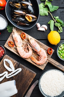 검은색 나무 탁자 위에 있는 나무 판자에 있는 해산물 새우 새우와 홍합, 꼭대기 전망, 음식 사진.