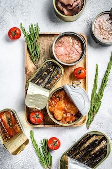 Закуски из морепродуктов - консервированные сардины, мидии, осьминоги, лосось и тунец. серый фон.