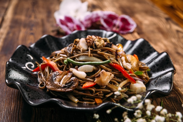 Seafood soba noodles wok in a black plate