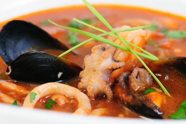 Seafood soup in white dish closeup