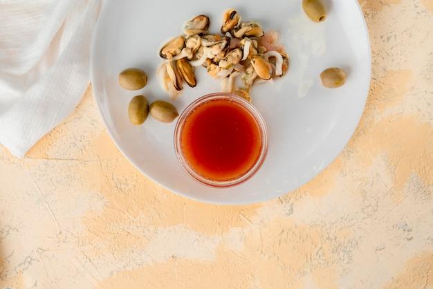 エビ、タコ、ムール貝などのシーフードとガラスのカップに入った特別なソース