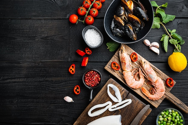 Seafood for traditional spanish paella specialties  over black wood table, flat lay with copy space Premium Photo