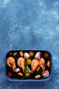 Seafood with black spaghetti in blue plate on blue background with copy space
