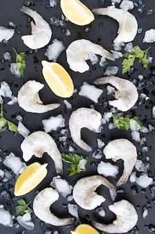 Морепродукты с лимонной петрушкой и льдом на темной поверхности, замороженные сырые креветки, королевские креветки на черном каменном фоне, поданная еда, приготовление здоровой пищи, кулинария, диета, концепция питания, концепция питания, вертикальный вид сверху
