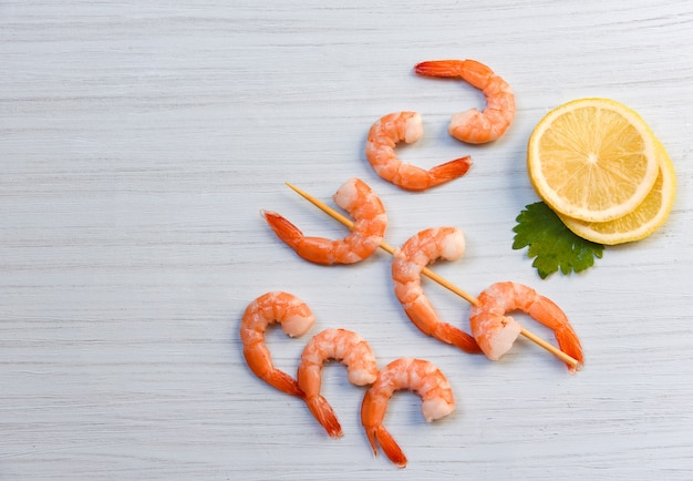 Seafood with shrimps prawns ocean gourmet dinner cooked with parsley lemon and skewers shrimp decorate on white wood background