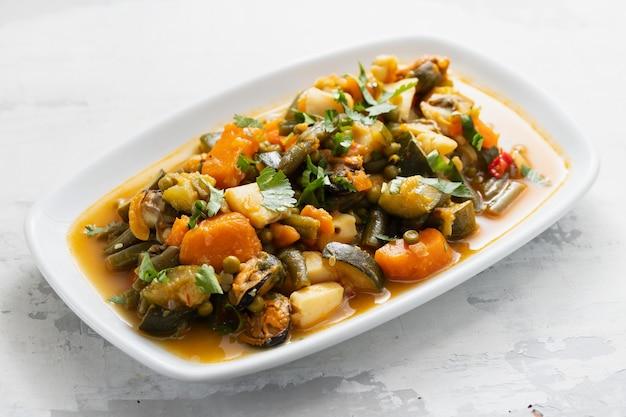 Морепродукты с овощами и зеленью на белом блюде
