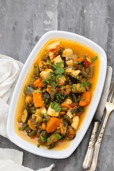 白い皿に野菜とハーブとシーフード