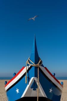 Чайка пролетает над носом лодки, пришвартованной на пляже назаре в португалии