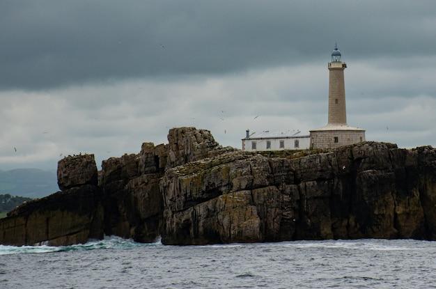 曇りの日の大きな岩の上に灯台がある海の風景