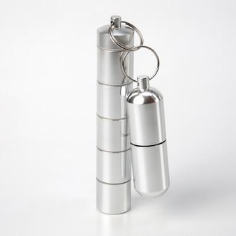 Герметичные алюминиевые контейнеры для мелких предметов и медицинских таблеток на белом фоне