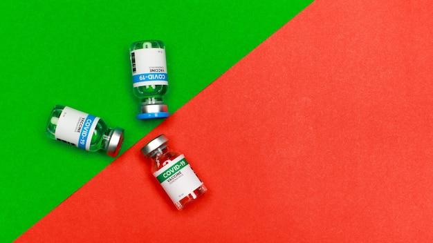 Запечатанные стеклянные флаконы с вакциной covid-19, 2 флакона в зеленой зоне и одна в красной заштрихованной области означает, что одной дозы лечения недостаточно для активации иммунитета и предотвращения вспышки заболевания.