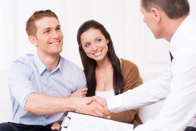 Заключение сделки. счастливый молодой человек, пожимая руку финансового агента, сидя вместе со своей женой