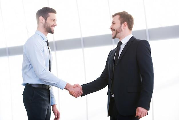 Заключение сделки. два веселых деловых человека, пожимая руки и улыбаясь, стоя в помещении
