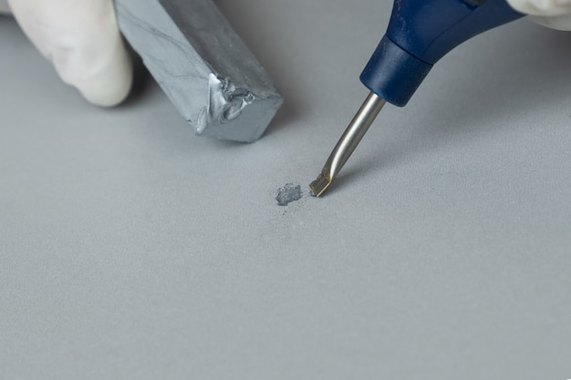 Sealing the defect on a wood surface with wax and of a soldering iron close-up.