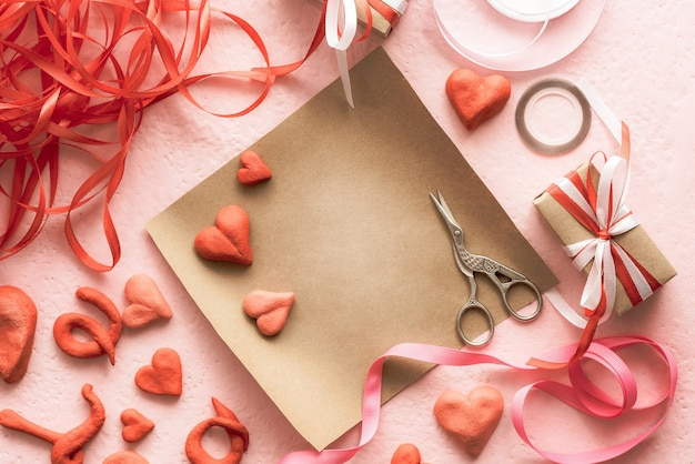 Sealing a valentine's day gift with colorful ribbons and pink hearts.