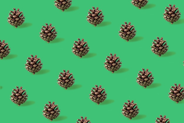 Seamless christmas pattern from pine cones on green background