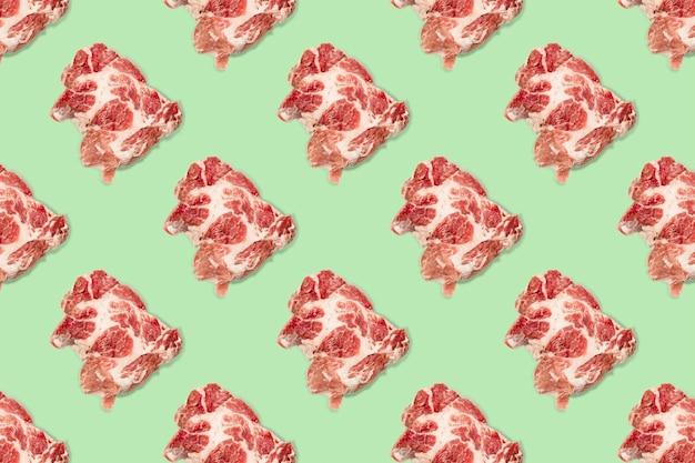 녹색 배경에 생 돼지고기 조각, 쇠고기 스테이크와 함께 매끄러운 음식 패턴입니다. 평면도. 평평하게 평평한 음식