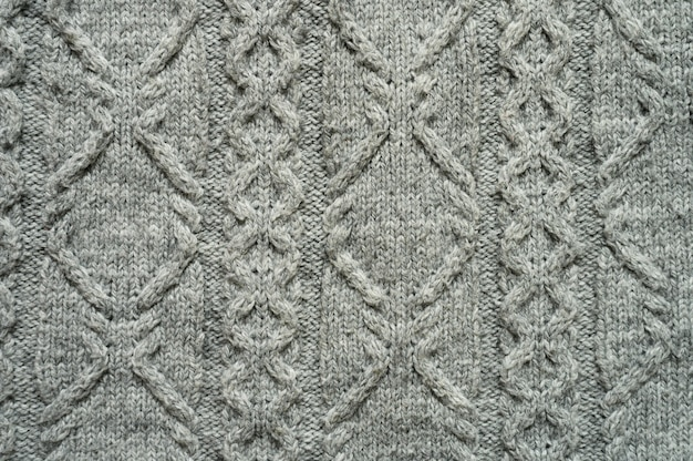 Seamless gray knitwear fabric texture with pigtails. knitting texture of sweater or scarf or plaid. knitted grey background. close up, top view.