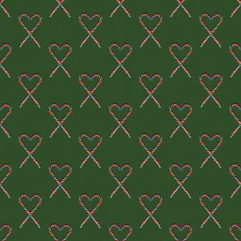 Бесшовные формы сердца с рождественскими конфетами на зеленом фоне, вид сверху. можно использовать в качестве декоративных элементов на рождество и новый год, день святого валентина.