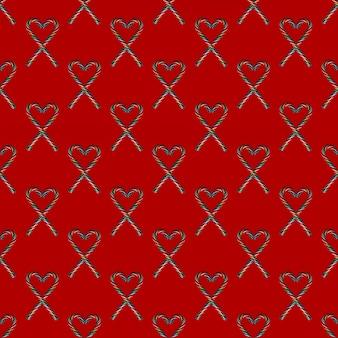 Бесшовные формы сердца с рождественскими конфетами на красном фоне, вид сверху. можно использовать в качестве декоративных элементов на рождество и новый год, день святого валентина.
