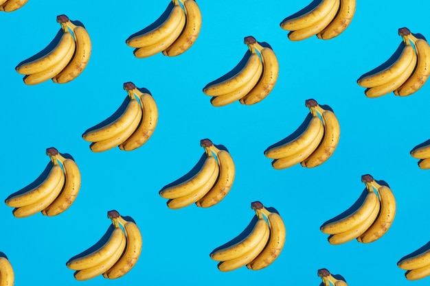Seamless light blue background with ripe yellow bananas pattern and hard dark shadows. new color trend 2021. minimal scene concept. tropical abstract pop art fruit image. free copy space.