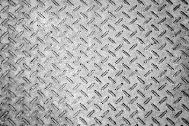 菱形のシームレスな金属のテクスチャ背景、アルミニウムまたはステンレスの暗いリスト