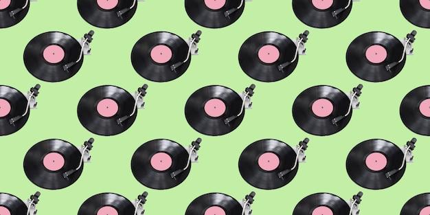 シームレスパターン。緑の背景に分離された抽象的なレコードプレーヤーの部分。ディスクジョッキーターンテーブルとビニール。レトロな音楽のコンセプト。
