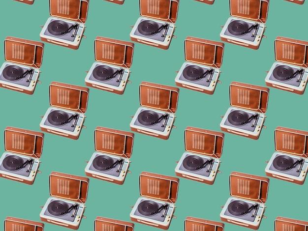 완벽 한 패턴입니다. 녹색 배경에 고립 된 추상 레코드 플레이어 부분입니다. 디스크 자키 턴테이블과 비닐. 레트로 음악 개념입니다.