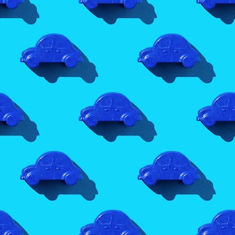 Seamless pattern of blue car toys on a blue background in bright light. the concept of selling and buying cars.