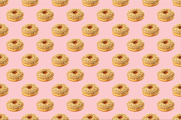 Seamless pattern of chocolate donuts sprinkled with nuts on pastel pink colors. donut pattern