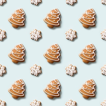 Seamless pattern of decorative cookies in shape of snowflakes and christmas tree