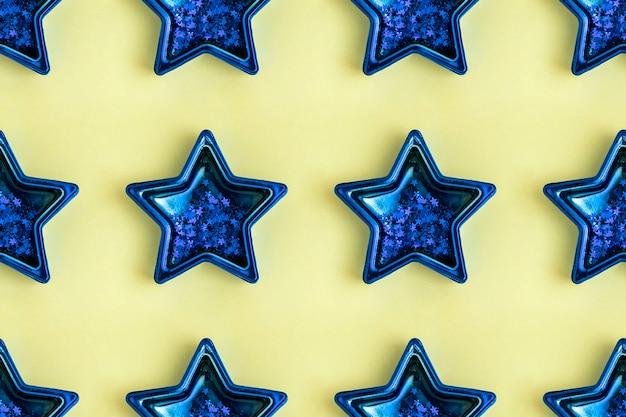 黄色の表面にある5つの尖った青い金属星からのシームレスなパターン。輝く装飾。