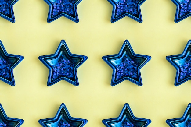 Seamless pattern from five pointed blue metallic star on yellow surface. shining decoration.