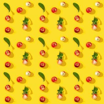 黄色の背景に熟した小さな赤いリンゴと緑の葉からのシームレスなパターン