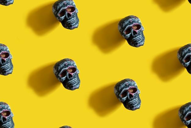 黄色の人間の頭蓋骨とのシームレスなパターンハロウィーンパーティーの背景