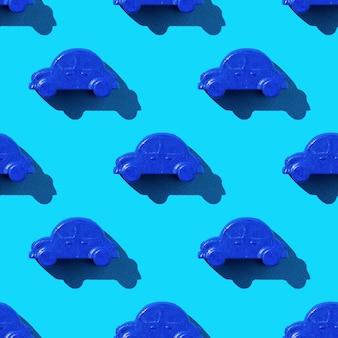 明るい光の中で青い背景に青い車のおもちゃのシームレスなパターン。車の売買の概念。