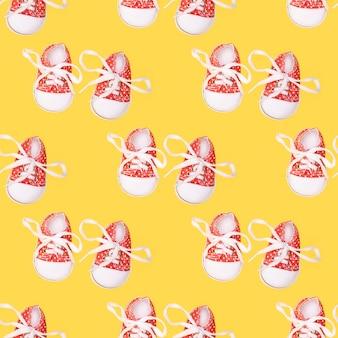 黄色の背景に子供の赤い靴のシームレスなパターン。高品質の写真