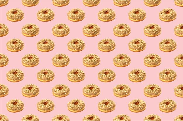 Бесшовный фон из шоколадных пончиков, посыпанных орехами в пастельных розовых тонах. пончиковый узор