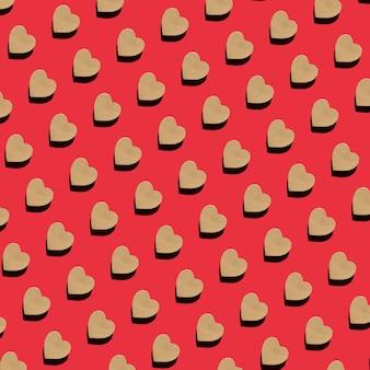 赤い背景の上面図フラットレイにハートの形をしたクラフトギフトボックスのシームレスなパターン。バレンタインのクリエイティブな構成。